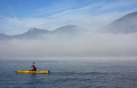 Man with a kayak in the fog