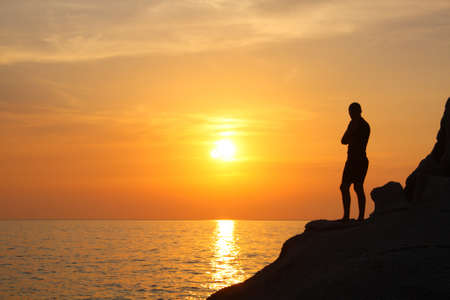 Silhouette of a man on a rock photo