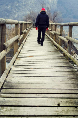 Man walking on the wooden bridge photo
