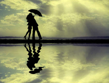 couple with umbrella at sunset photo
