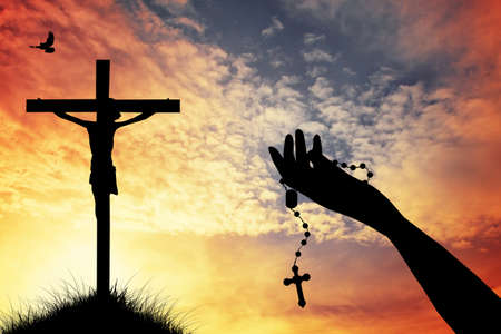 woman praying with rosary Stock Photo