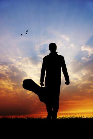 Mann mit Gitarre bei Sonnenuntergang