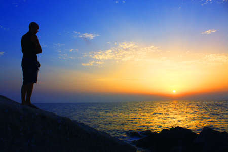 man on the cliff at sunset photo