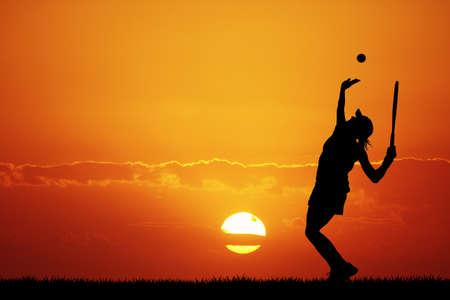 girl playing tennis at sunset photo