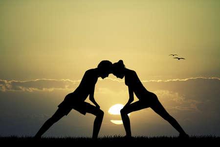 couple doing yoga at sunset
