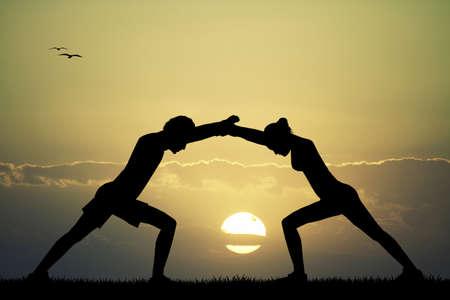 couple doing yoga at sunset photo