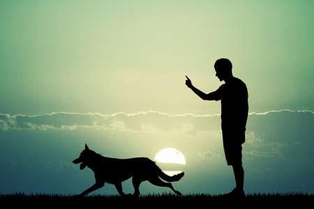 zooth�rapie: homme chien de formation au coucher du soleil Banque d'images