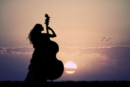 double bass: woman plays the double bass at sunset