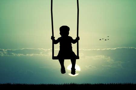 child on swing ilhouette at sunset