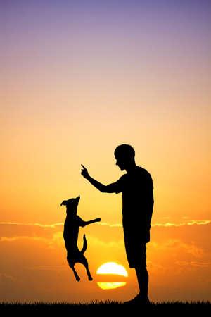 zooth�rapie: homme et le chien au coucher du soleil Banque d'images