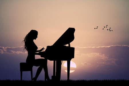 女性は日没でピアノを弾く