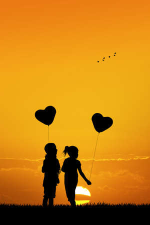 two children: children with balloons at sunset Stock Photo