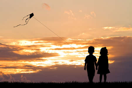 happiness people silhouette on the sunset: children with kite at sunset Stock Photo