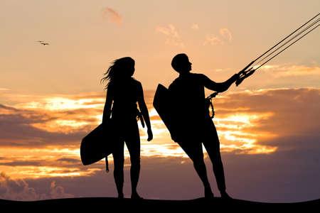 surfers paar bij zonsondergang Stockfoto