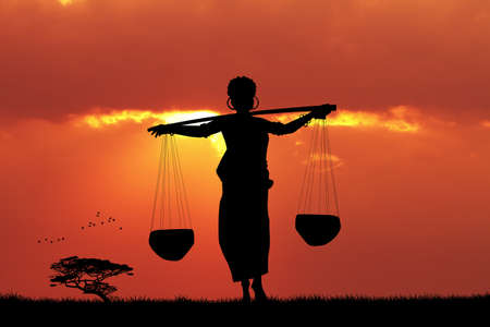 carrying: African woman carrying water at sunset Stock Photo