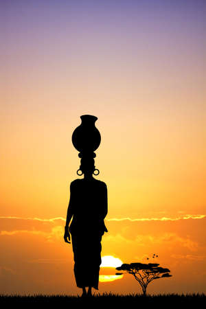 African woman silhouette at sunset Stock Photo