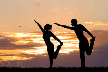 yoga sunset: couple doing yoga at sunset
