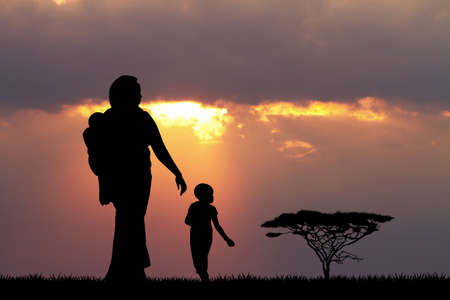 reflection of life: African woman and child at sunset Stock Photo
