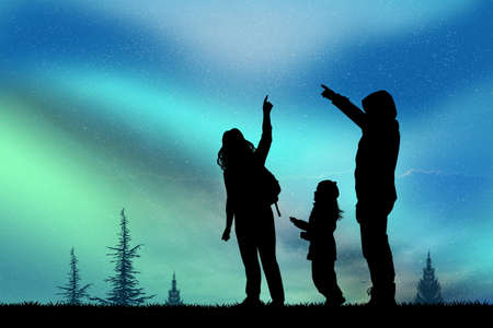 mountain silhouette: people look at the northern lights