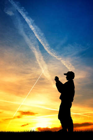 man looking at sky: boy makes the photo at sunset with their cell phone