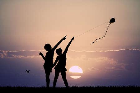girls with kite at sunset Stock Photo