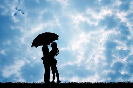 innamorati che si baciano: coppia con ombrello sotto la pioggia