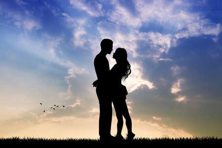 enamorados besandose: amantes que se besan en la puesta del sol