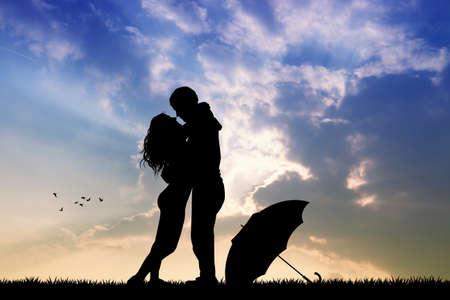innamorati che si baciano: paio sotto la pioggia al tramonto Archivio Fotografico