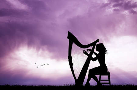 woman playing the harp at sunset Stock Photo
