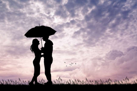 melancholy: romantic couple with umbrella at sunset