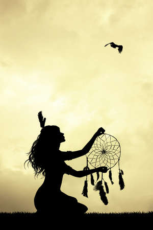 nature woman: girl with dreamcatcher at sunset