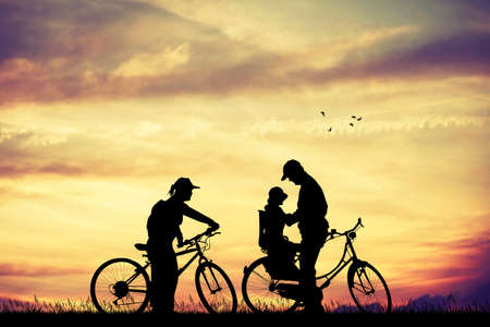 Family on bicycle at sunset Stock Photo