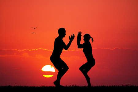 meditation man: couple doing yoga at dawn