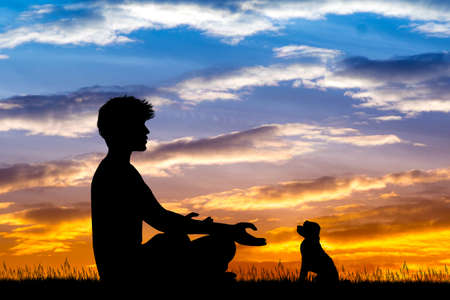 man doing yoga with dog at sunset Stock Photo