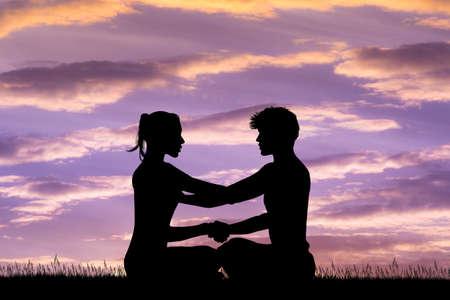 man and woman doing yoga at sunset Stock Photo