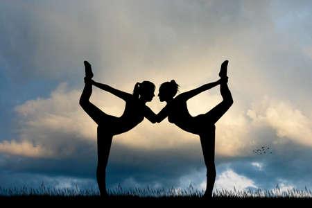 two girls do yoga at sunset Reklamní fotografie
