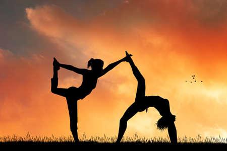 two women do yoga poses at dawn Reklamní fotografie