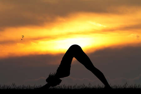 down dog yoga pose at sunset Stock Photo