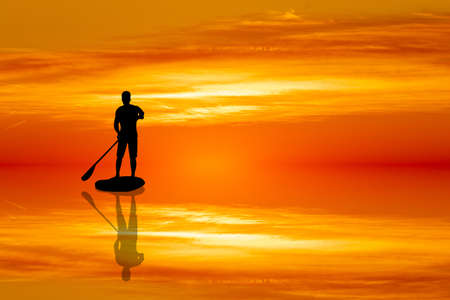 Man on paddle at sunset