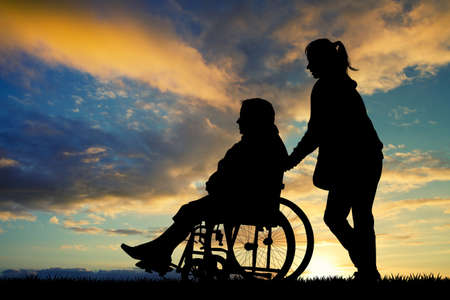 daughter accompanies her mother in wheelchair Reklamní fotografie