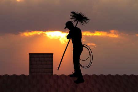 kominiarz na dachu o zachodzie słońca