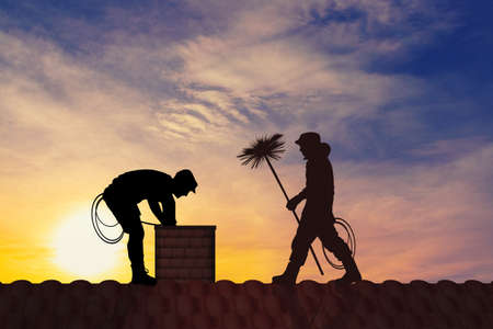 chimney sweep on the roof at sunset Banco de Imagens