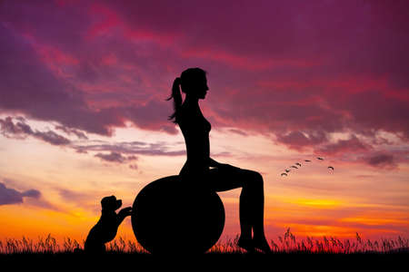 girl does pilates at sunset with her puppy Stock Photo