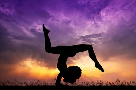 silhouette of girl yoga pose at sunset