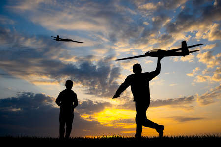 men with remote controlled airplanes at sunset Banque d'images - 126911819