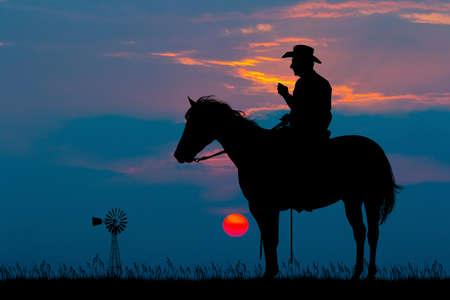 cowboy on horse at sunset Stock Photo