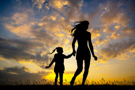 girl runs with her daughter at sunset Stockfoto