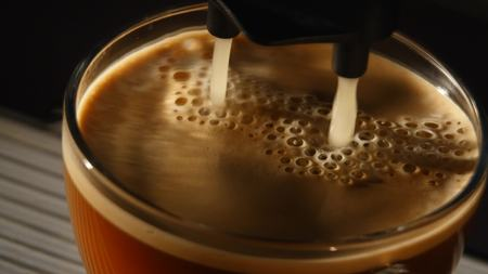 coffee machine pouring espresso in cup extremely close-up.
