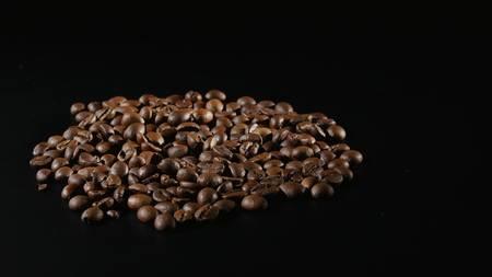 Geröstete Kaffeebohnen Drehen auf schwarzem Hintergrund Standard-Bild