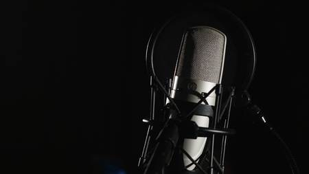 Microphone on a stand located in a music studio recording booth under low key light. Foto de archivo
